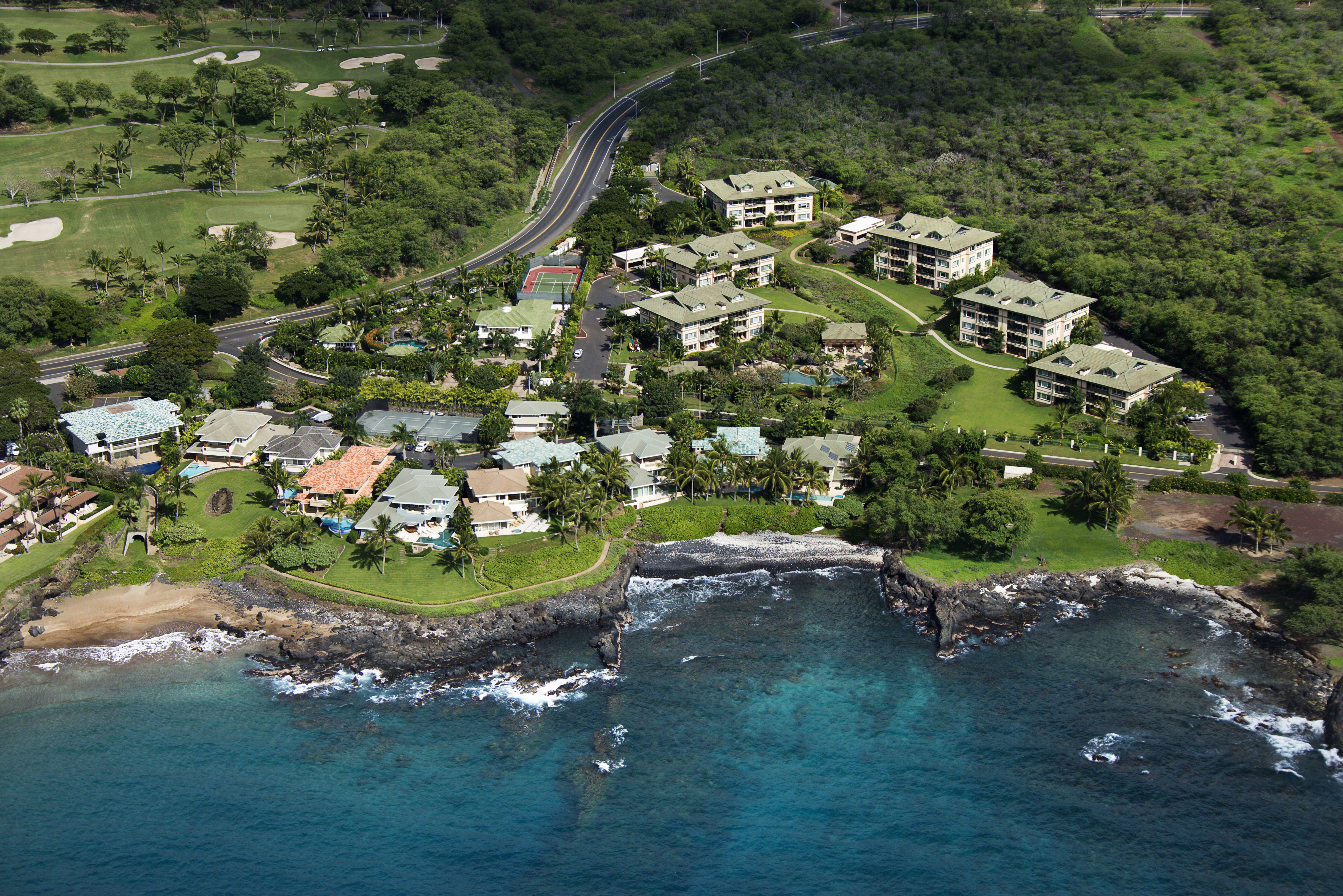 Aerial of houses clustered by Maui, Hawaii coast.