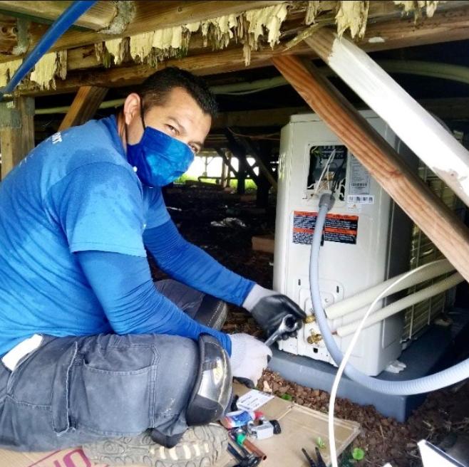An AC technician repairing a unit.