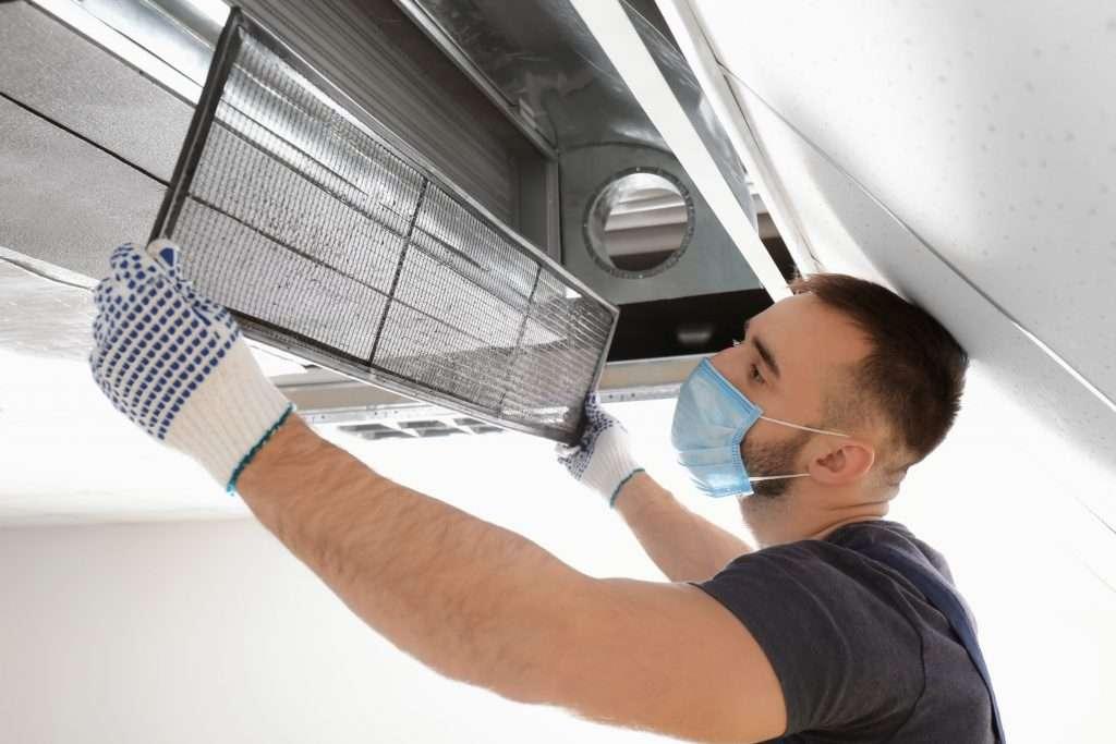 man changing filter to provide HVAC maintenance